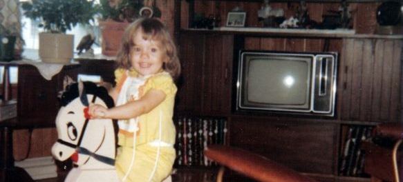 Young Jaime on a rocking horse with a very 1970s television in the background and a cowlick that could part the Red Sea.