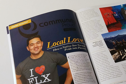 "Magazine open to article spread picturing smiling man in ""I heart FLX"" tshirt."
